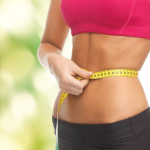 fitness and diet concept - close up of trained belly with measuring tape